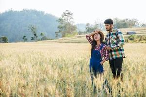 Farming couple looking out at barley field in harvesting season photo