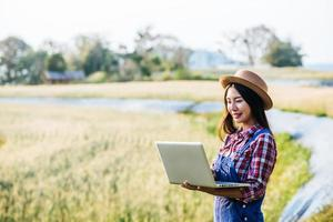 Smart woman farmer looking at barley field with laptop computer photo