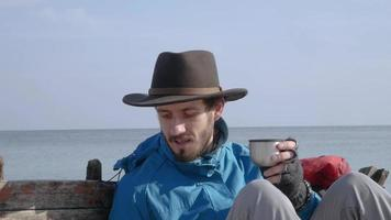 jeune homme près d'un bateau en bois sur la plage video