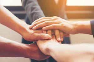 Manos del equipo empresarial mostrando unidad con poner sus manos juntas foto