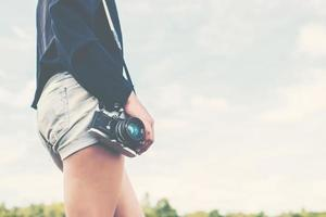 Fotógrafo de mujeres hermosas de pie mano sosteniendo una cámara retro foto