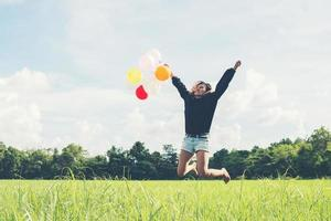 Hermosa mujer sosteniendo un globo sobre la hierba verde corriendo y saltando foto