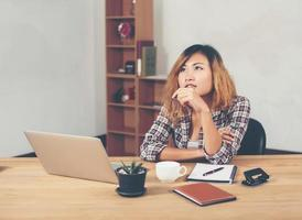 Young beautiful hipster woman sitting on workplace and thinking photo