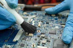 Technician use brush to clean dust in circuit board computer. photo