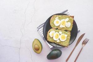 Avocado and egg on slice of a brown bread on white background photo