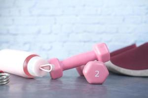pink color dumbbell, exercise mat and water bottle on white background photo
