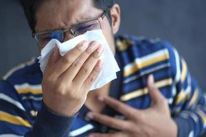 enfermo con gripe sonarse la nariz con una servilleta. foto