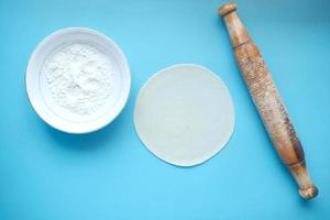baking dough with rolling pin on table, top view photo