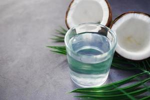 slice of fresh coconut and glass of coconut water on table photo