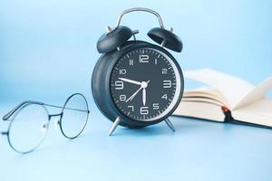 reloj despertador, anteojos y libro sobre la mesa foto