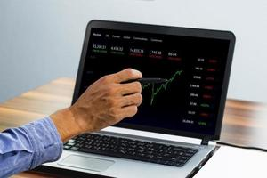 Man point on screen digital chart trading online at home photo