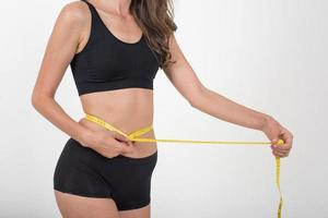 Portrait of beautiful young woman measuring her figure size with tape measure photo