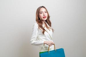 Portrait beautiful Asian woman holding shopping bag on white background photo