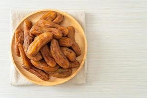 Sun-dried banana on wooden plate photo
