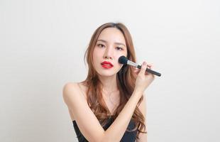 Portrait beautiful Asian woman with makeup brush on white background photo
