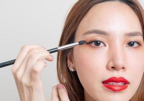 Retrato hermosa mujer asiática con pincel de maquillaje sobre fondo blanco. foto