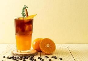 A glass of iced Americano black coffee and layer of orange and lemon juice decorated with rosemary and cinnamon photo