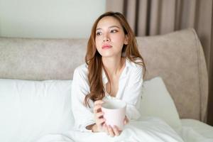 retrato, hermoso, mujer asiática, despertar, y, tenencia, taza de café, o, taza, en cama, por la mañana foto