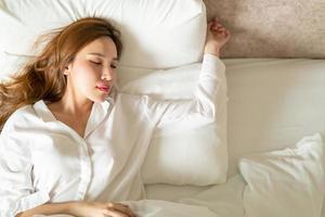 Retrato hermosa mujer asiática durmiendo en la cama con almohada blanca foto