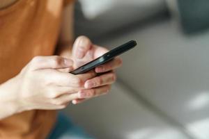 mujer joven con smartphone escribiendo, charlando conversación. tecnología foto