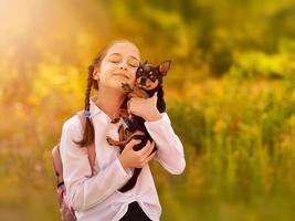 niña colegiala sosteniendo y jugando con perro mascota. amigos. foto