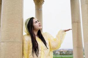 Beautiful brunette woman in yellow raincoat catching rain outdoors photo