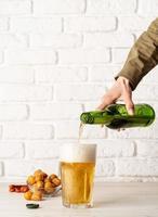 Cerveza vertiendo de botella en vidrio, fondo de pared de ladrillo blanco. foto