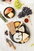 Cheese plate assortment served with honey, grapes, bread and rosemary photo