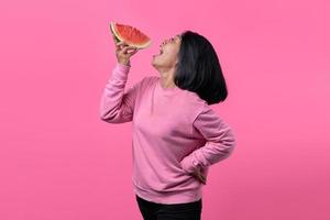 Attractive young Asian woman holding watermelon pieces photo