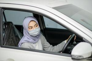 Woman wearing protection mask in car photo
