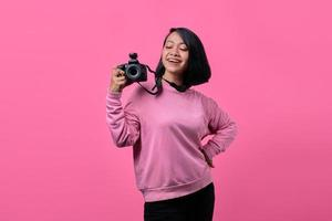 Happy smiling young woman holding camera on pink background photo