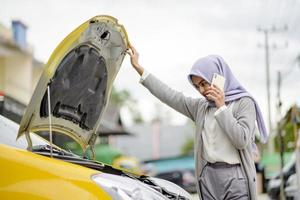 Portrait of Asian woman busy calling repair shop for service photo