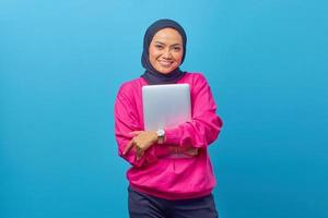 Portrait of beautiful smiling college student  holding laptop photo