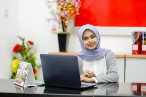 Portrait of Asian woman sitting smiling in front of laptop photo