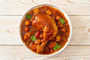 Homemade chicken stew with tomatoes, onions, carrot, and potatoes on plate photo