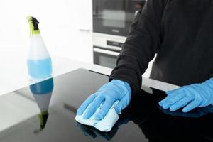 Hands in protective glove cleaning a modern electric stove with rag photo