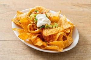 Mexican nachos tortilla chips with jalapeno, guacamole, tomatoes salsa and dip photo