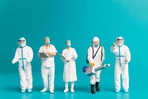 Equipo en miniatura de médicos hombres y mujeres que luchan contra enfermedades y virus. foto