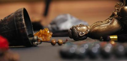 Close up of occult altar with figurine of Buddha, stone rosaries photo