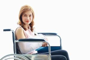 Asian woman has a broken arm wearing a cast setting on wheelchair photo