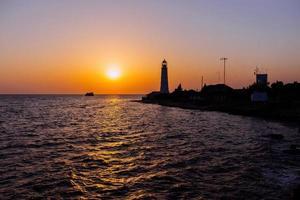 Lighthouse on the sea coast at sunset photo