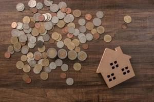 money coins growing with wood house model photo