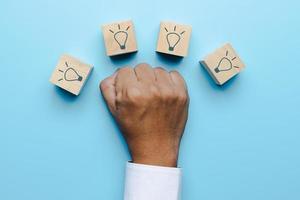 mano del hombre de negocios muestra a la lucha con la idea al logro foto