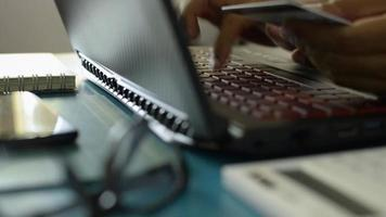 homme tenant une carte de crédit en tapant un clavier d'ordinateur portable pour le paiement en ligne. video