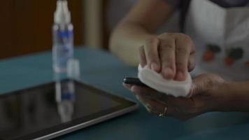 Woman cleaning and disinfection on surfaces of mobile phone. video