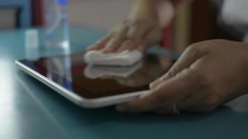 femme nettoyant et désinfectant sur les surfaces de la tablette numérique. video