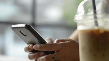 mujer charlando en las redes sociales en línea con el teléfono móvil bebiendo café con hielo. video