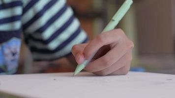 Schoolgirl drawing on a paper with pencil at home. video