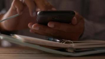 manos del empresario mediante teléfono inteligente móvil en la mesa de trabajo. video