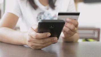 femme faisant des achats en ligne sur smartphone avec carte de crédit à la maison. video